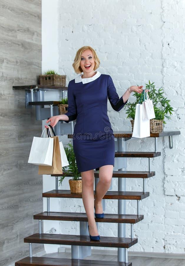 Mulher de sorriso feliz nova com os sacos de compras nas escadas foto de stock royalty free