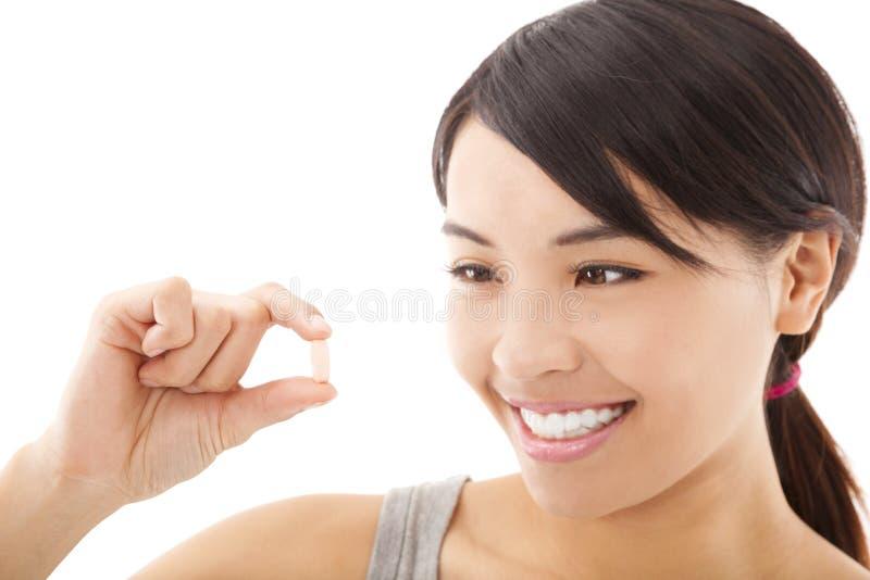 Mulher de sorriso feliz nova que mostra a vitamina fotografia de stock