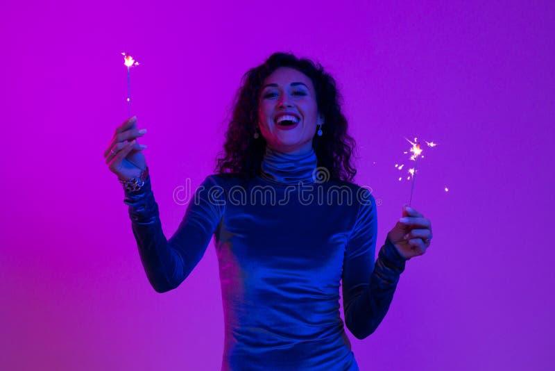 Mulher de sorriso feliz que comemora com fogos-de-artifício Menina que guarda um partido claro do ano novo de bengal fotos de stock royalty free