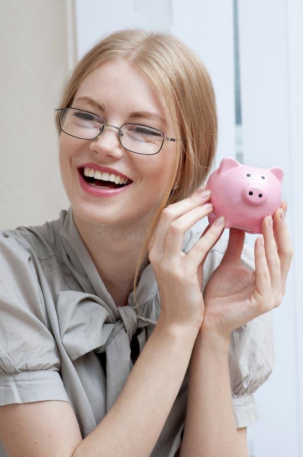 Mulher de sorriso feliz que guarda o mealheiro fotos de stock royalty free