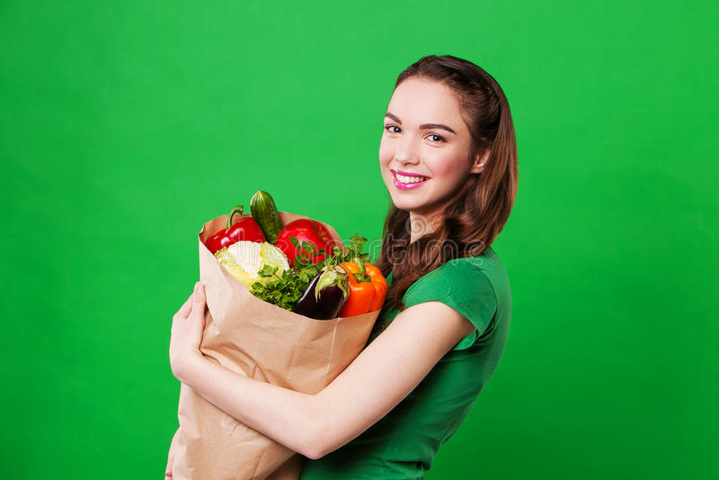 Mulher de sorriso feliz que mantém um saco de mantimento completo do alimento fresco e saudável fotos de stock royalty free