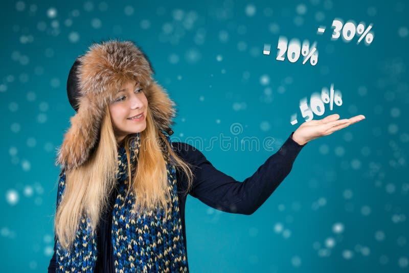 Mulher de sorriso feliz que mostra apontando em discontos 50%, 30%, 20% Conceito da venda do inverno fotos de stock royalty free
