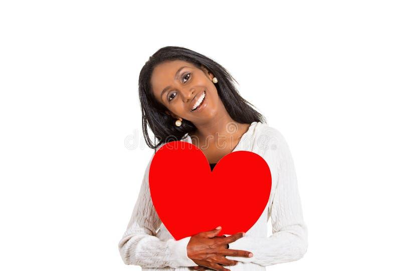 Mulher de sorriso feliz que olha o grande coração vermelho da terra arrendada entusiasmado fotos de stock