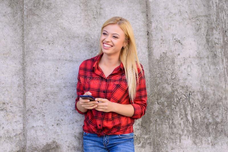 Mulher de sorriso feliz que usa seu smartphone para datilografar com telephon engraçado funky do móbil do riso do riso da alegria fotos de stock royalty free