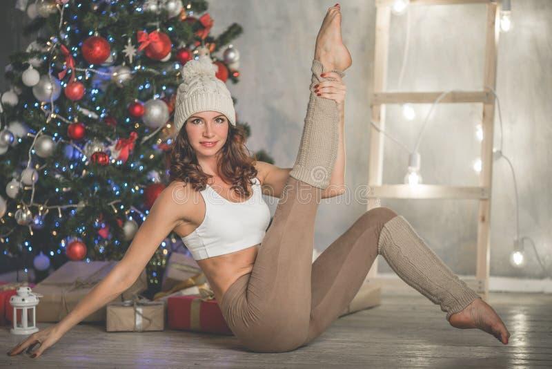A mulher de sorriso flexível bonita com caixa de presente está fazendo esticando a árvore em casa próximo decorada do xmas da for fotos de stock