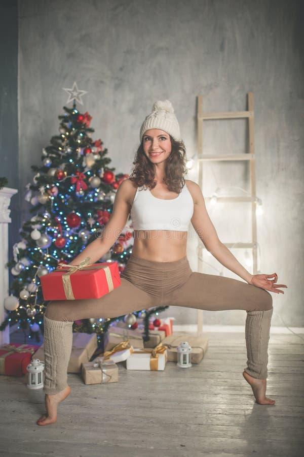 A mulher de sorriso flexível bonita com caixa de presente está fazendo esticando a árvore em casa próximo decorada do xmas da for imagem de stock