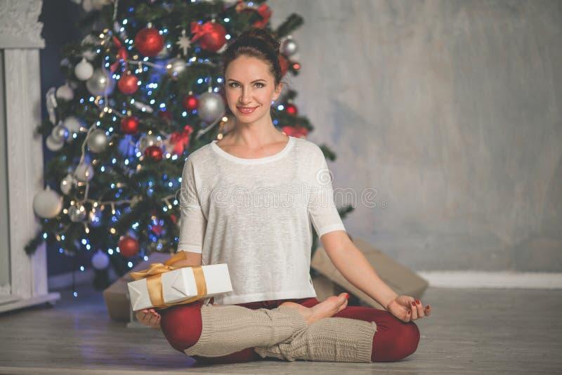 A mulher de sorriso flexível bonita está fazendo esticando a árvore em casa próximo decorada do xmas da forma do exercício, os es fotos de stock royalty free