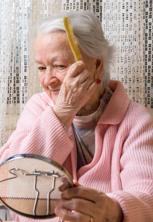 Mulher de sorriso idosa que penteia seu cabelo imagens de stock