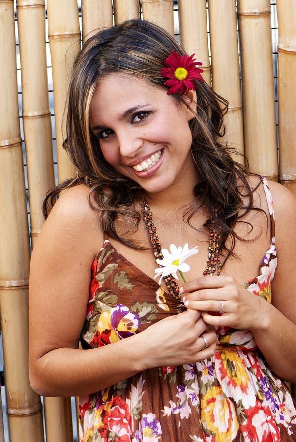 Mulher de sorriso latin bonita com uma flor foto de stock royalty free