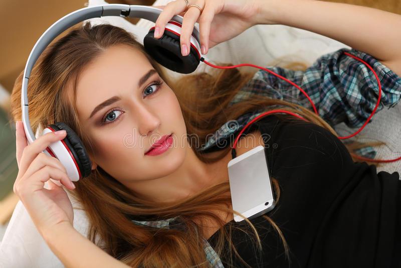 A mulher de sorriso loura bonita posta sobre ou decola fones de ouvido imagens de stock