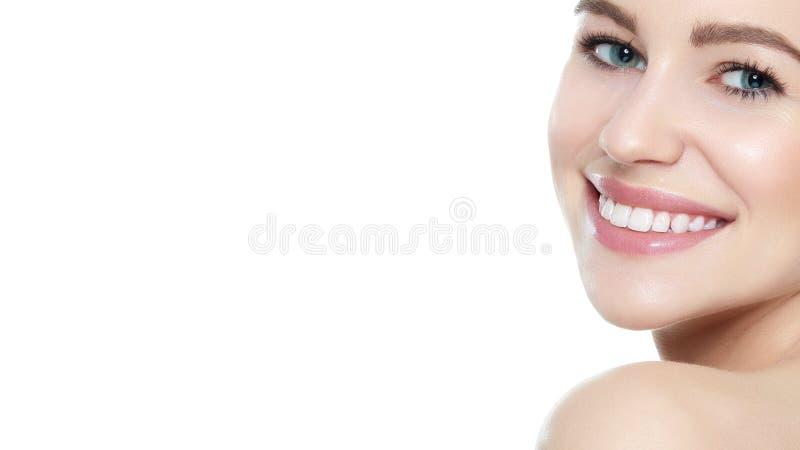 A mulher de sorriso loura nova bonita com pele limpa, a composição natural e aperfeiçoam os dentes brancos, no fundo branco fotografia de stock royalty free
