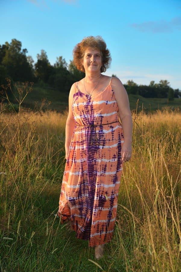 Mulher de sorriso madura que anda no campo no dia ensolarado imagem de stock royalty free
