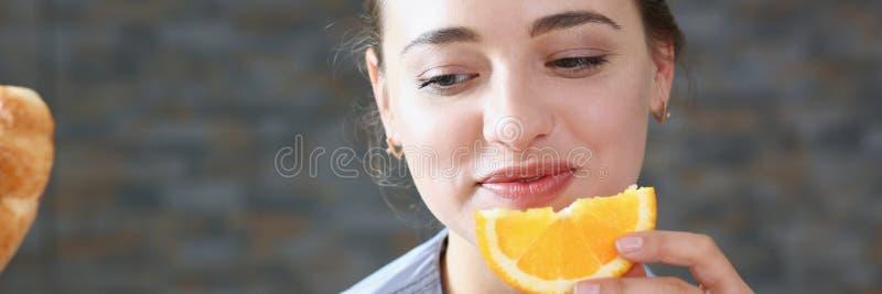 A mulher de sorriso moreno bonita come a laranja cortada fotografia de stock royalty free