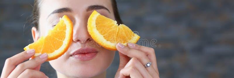 A mulher de sorriso moreno bonita come a laranja cortada imagens de stock royalty free