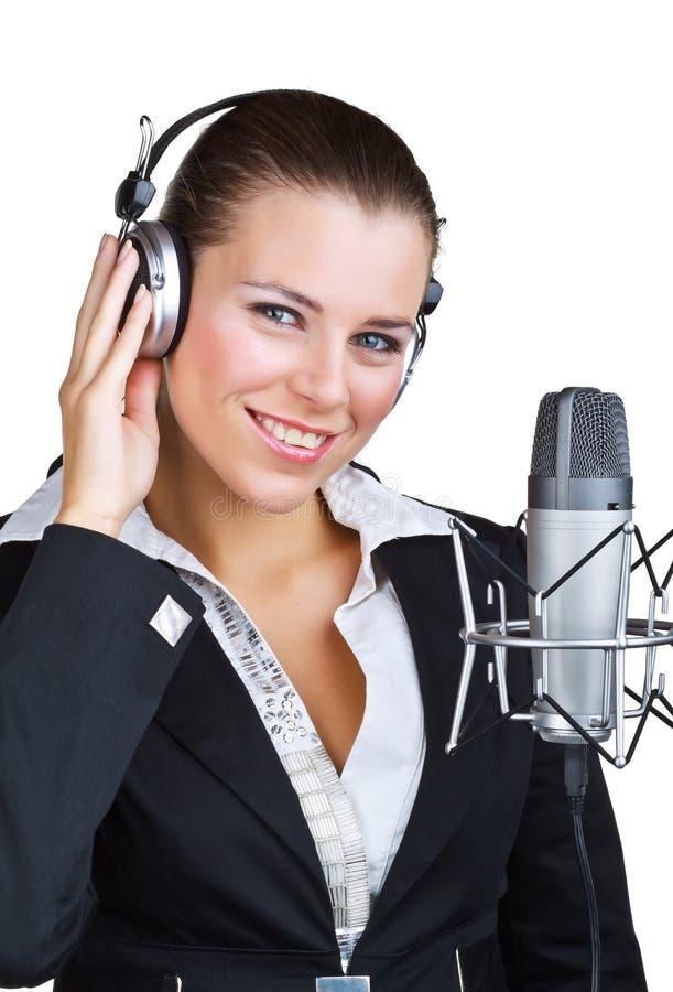 Mulher de sorriso na frente de uns auriculares do microfone foto de stock