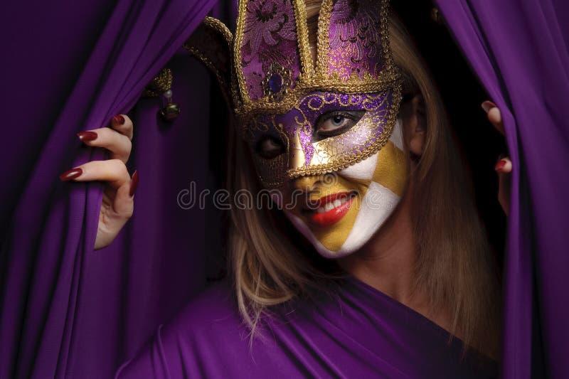 Mulher de sorriso na máscara violeta fotos de stock
