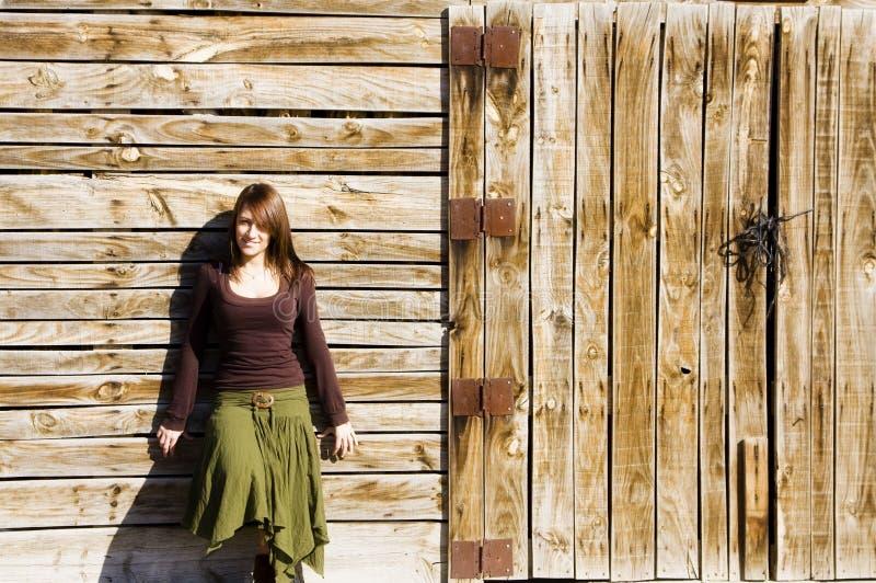Mulher de sorriso na parede de madeira foto de stock