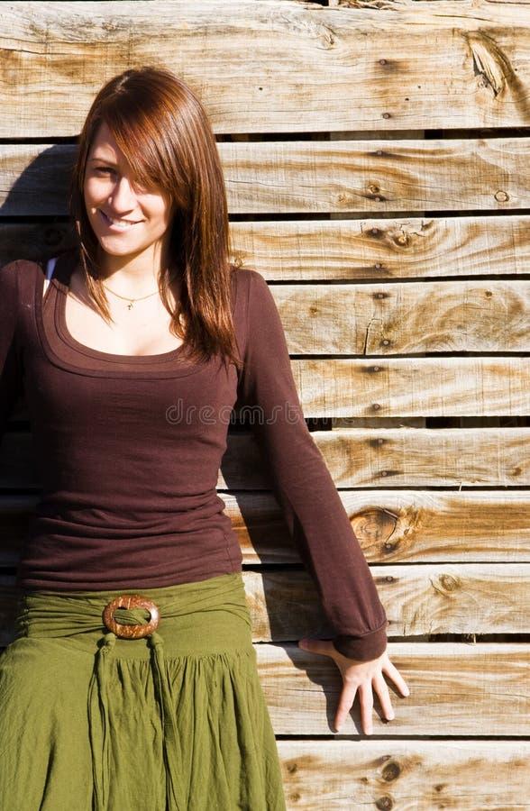 Mulher de sorriso na parede de madeira fotos de stock royalty free