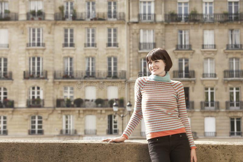 Mulher de sorriso na ponte contra casas de cidade fotografia de stock
