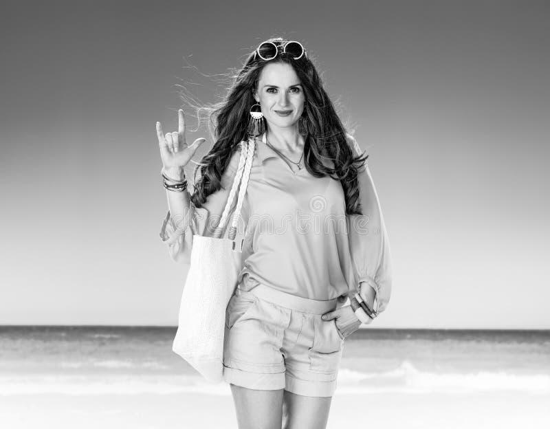 Mulher de sorriso na praia que mostra eu te amo o gesto de mão foto de stock