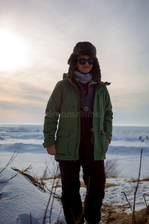 Mulher de sorriso na roupa do inverno na costa congelada do lago durante o sol imagens de stock