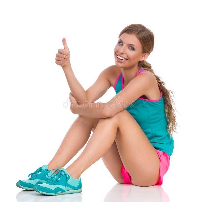 Mulher de sorriso na roupa dos esportes que senta-se no assoalho e que mostra o polegar acima imagem de stock