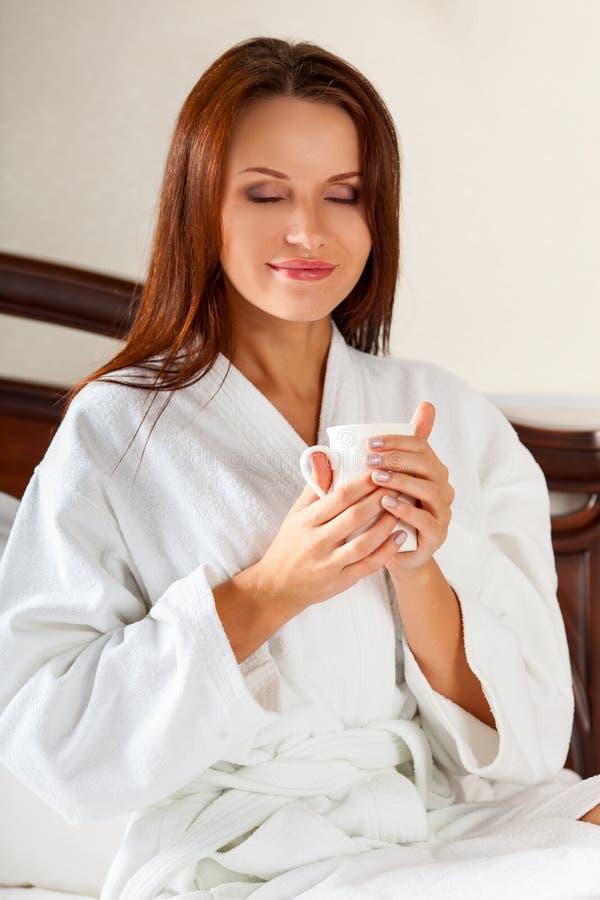 Mulher de sorriso no café bebendo do quarto na cama fotografia de stock