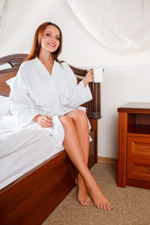 Mulher de sorriso no café bebendo do quarto na cama foto de stock royalty free