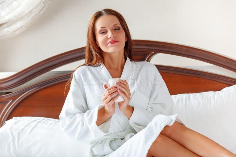 Mulher de sorriso no café bebendo do quarto na cama fotos de stock