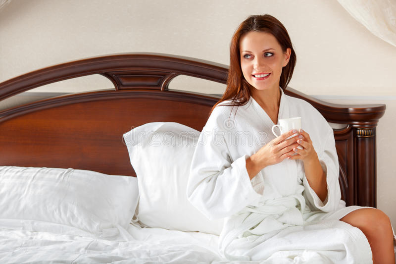 Mulher de sorriso no café bebendo do quarto na cama imagem de stock