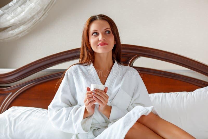 Mulher de sorriso no café bebendo do quarto na cama foto de stock