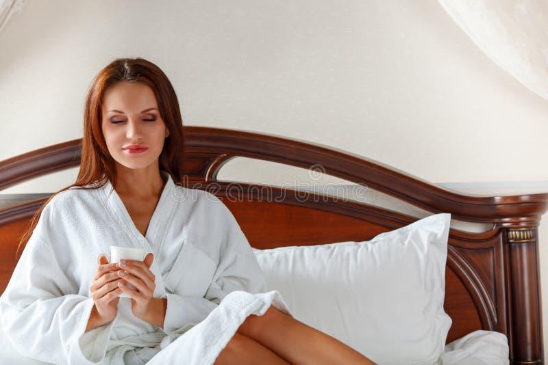 Mulher de sorriso no café bebendo do quarto na cama imagens de stock