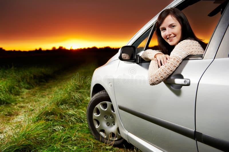 Mulher de sorriso no carro no por do sol fotos de stock