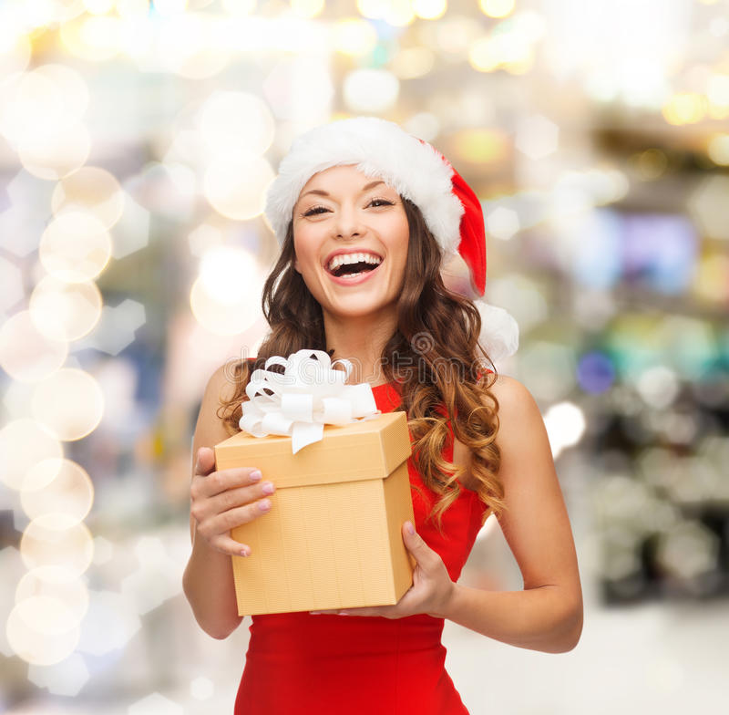 Mulher de sorriso no chapéu do ajudante de Santa com caixa de presente imagens de stock royalty free