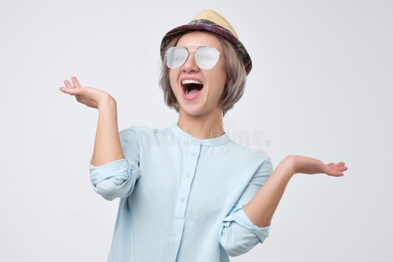 Mulher de sorriso no chapéu e na encolho de ombros dos vidros do verão suas mãos acima foto de stock royalty free