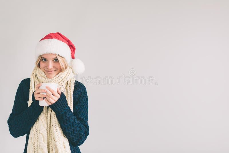 Mulher de sorriso no chapéu de Santa com a xícara de café, isolada no branco A menina é vestida na camiseta, tampão do Natal e foto de stock royalty free