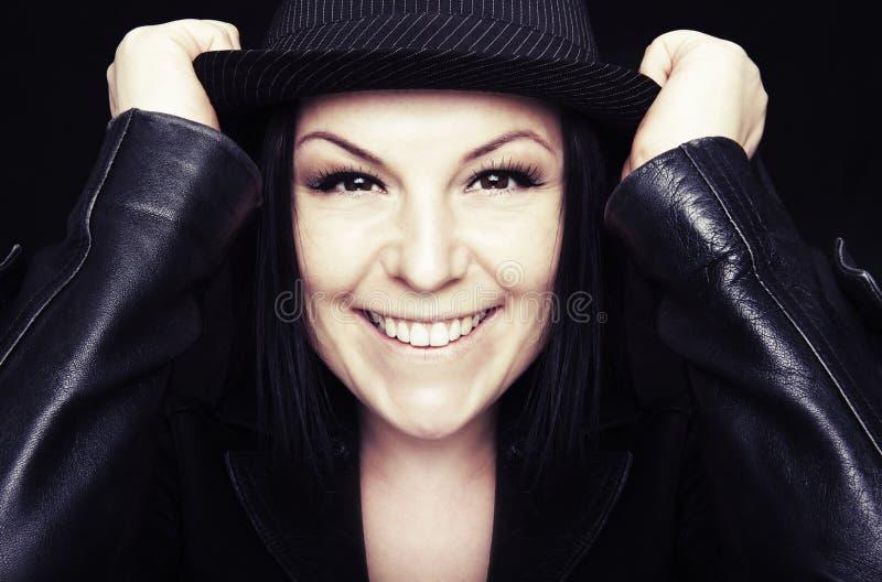 Mulher de sorriso no chapéu sobre a obscuridade fotos de stock royalty free