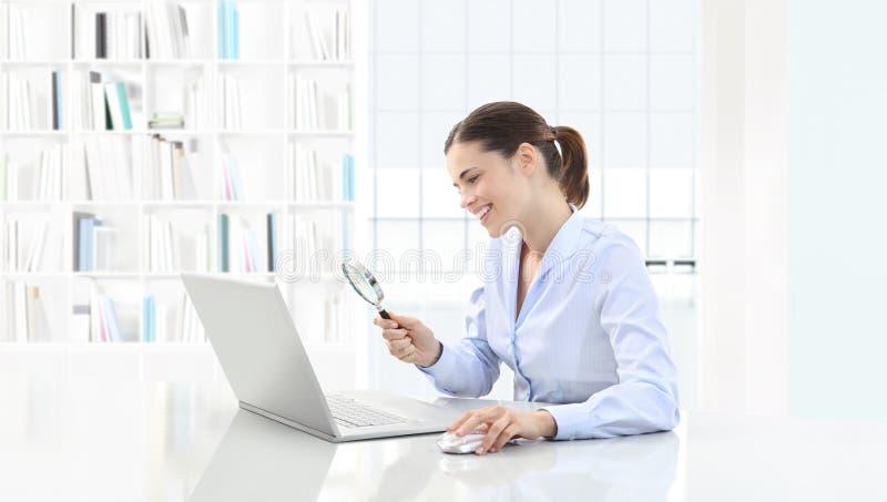 A mulher de sorriso no escritório procura no computador com lupa fotografia de stock