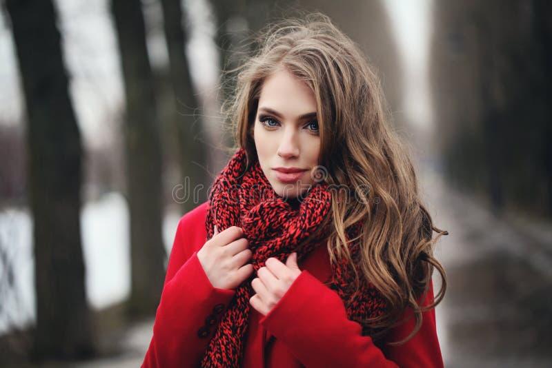 Mulher de sorriso no lenço vermelho que anda no parque fotos de stock royalty free