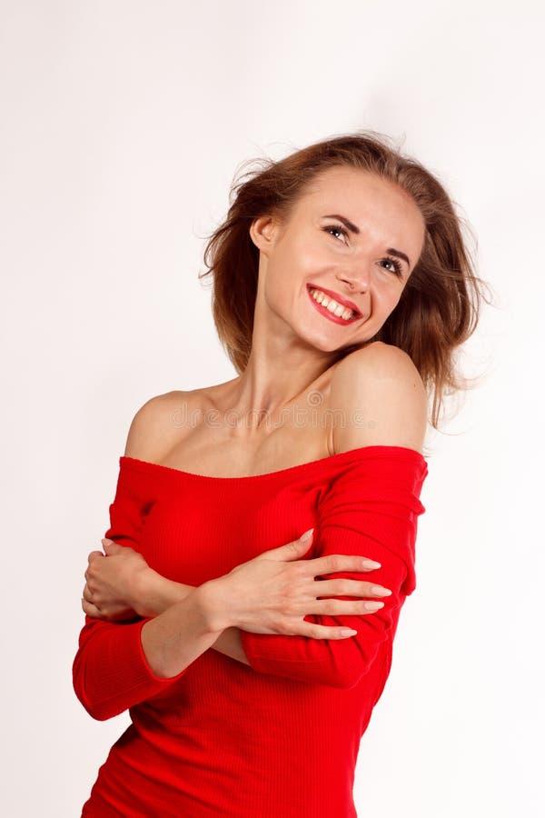 Mulher de sorriso no levantamento vermelho contra o fundo branco iso do estúdio fotos de stock royalty free