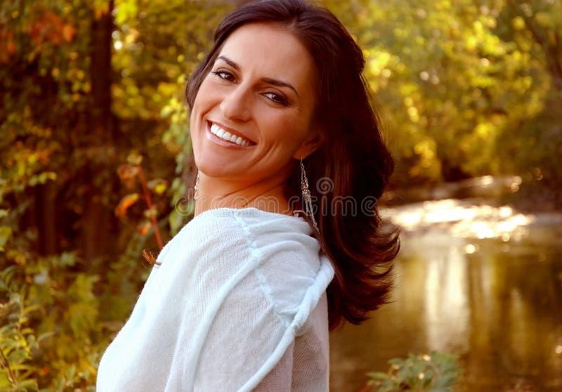 Mulher de sorriso no outono fotografia de stock