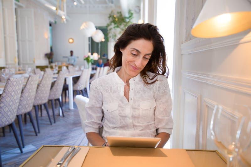 Mulher de sorriso no restaurante que lê a tabuleta digital imagens de stock