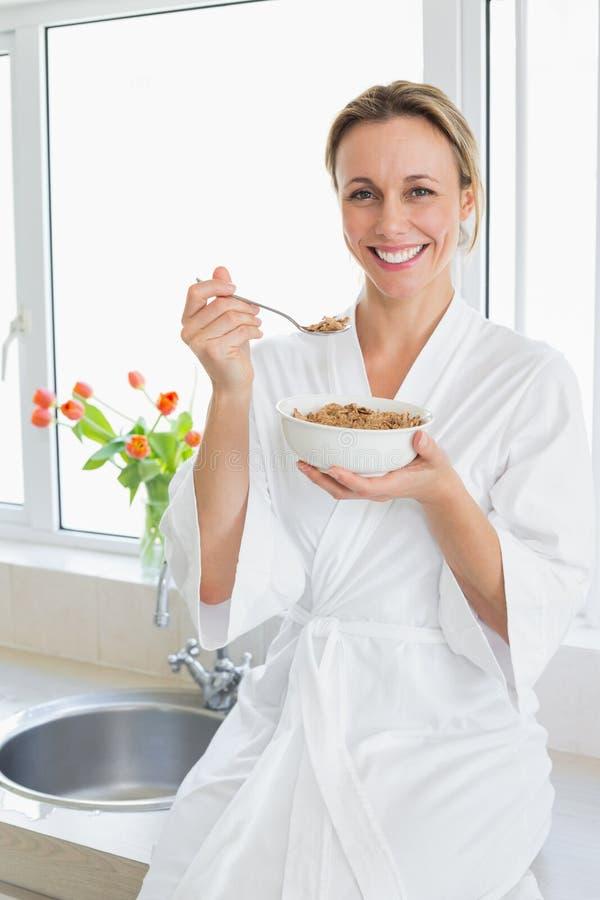Mulher de sorriso no roupão que come o cereal foto de stock royalty free
