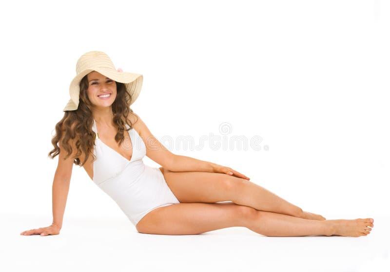 Mulher de sorriso no roupa de banho e no chapéu que colocam no assoalho imagem de stock royalty free