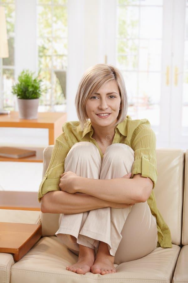 Mulher de sorriso no sofá fotografia de stock