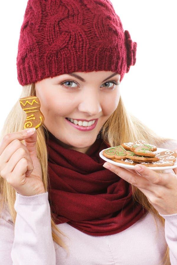 Mulher de sorriso no tampão de lã e no xaile que guardam pão-de-espécie, tempo do Natal imagem de stock