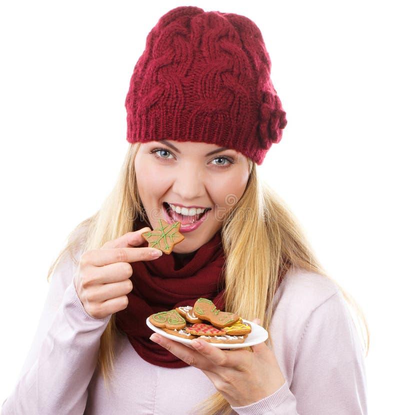Mulher de sorriso no tampão de lã e no xaile que guardam pão-de-espécie, tempo do Natal imagens de stock royalty free