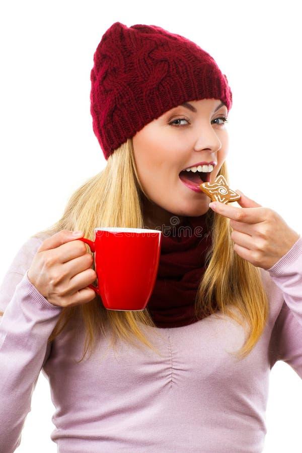 Mulher de sorriso no tampão e no xaile de lã com cookies do pão-de-espécie e chá, fundo branco, tempo do Natal foto de stock royalty free