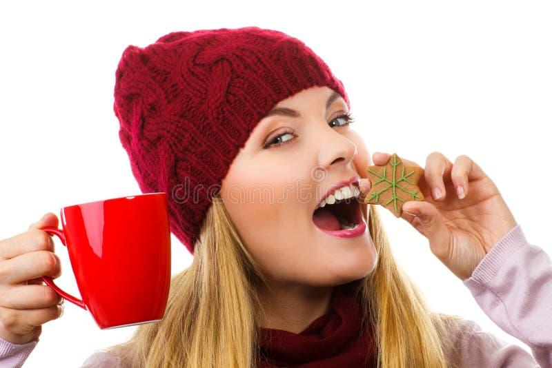 Mulher de sorriso no tampão e no xaile de lã com cookies do pão-de-espécie e chá, fundo branco, tempo do Natal fotos de stock royalty free