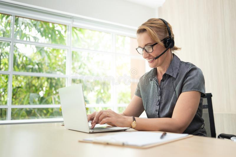 Mulher de sorriso no trabalho no portátil e nos auriculares no centro de atendimento fotografia de stock